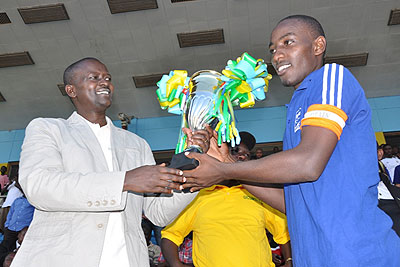 The Ministry of Sport's Permanent Secretary Edward Kalisa presents the second division league title to Esperance Fc captain on Sunday after the climax of the lower division season.