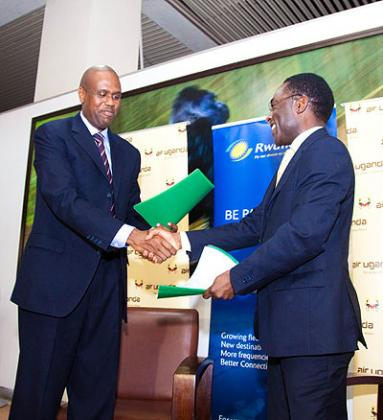 RwandAir CEO John Mirenge (left) and Cornwell Muleya, the Air Uganda boss, exchange documents after signing the deal. The New Times / Timothy Kisambira