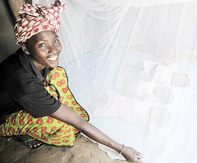 A mother lays mosquito nets over begging for children to sleep in. Scientists are closer to using malaria vaccine. Net photos.