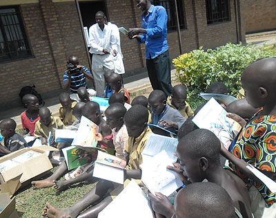 Pupils read books donated by Bakeme Editions. The New Times/ Susan Babijja.