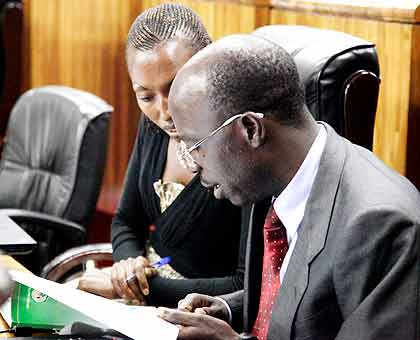 MPs Manirora Annoncee (L) and Theobald Mporanyi scrutinise the Ombudsman report yesterday. The New Times/ John Mbanda.