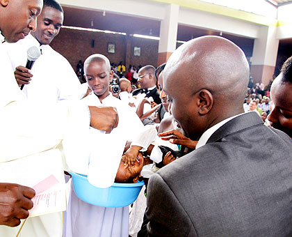 Father Andrew Baributsa (L) baptises a child at Saint Michel Cathedral in Kigali on Christmas Day. The New Times/Timothy Kisambira