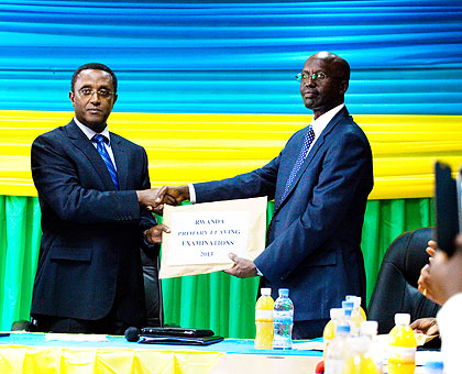 Dr Biruta (L) receives an envelope containing results from Dr John Rutayisire, the director-general of Rwanda Education Board, at the Board offices in Remera, Kigali, yesterday. The New Times/ Timothy Kisambira.