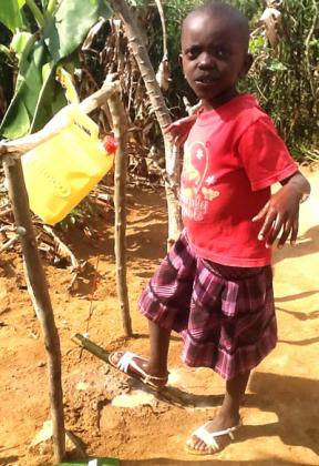 Umutesi uses Step-and-Wash apparatus at her family home compound. Seraphine Habimana.