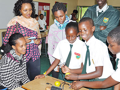 Students carry out an experiment as their parents look on in admiration. (Courtesy)