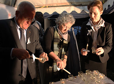Amb. Maenner (L) and Schieber (C) light candles in honour of GTZ and DED victims. Courtesy.
