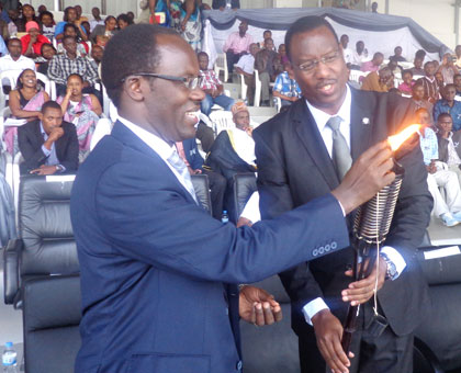 City of Kigali mayor Fidele Ndayisaba (L) and Culture and Sports minister Protais Mitali  light the Flame of Hope in honour of City employees killed during Genocide. Jean Tabaro.