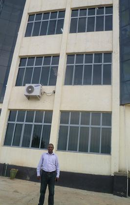 Ndagijimana in front of one of his commercial buildings, which houses banks like KCB among other businesses. The New Times / Seraphine Habimana.