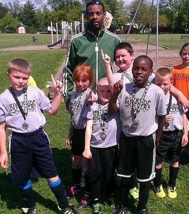 Moses Kamanzi poses with a group of youngsters at his Ohio-based Riverside Youth Soccer Club. Courtesy.