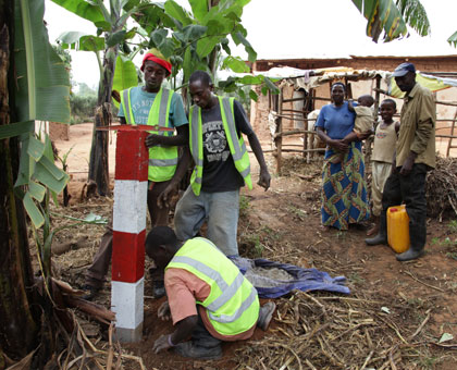 Nizeyimana and his family (R) look on as a demarcation beacon is erected in their compound in Busanza, Kicukiro District. John Mbanda. File.