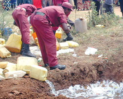 Local Defence Unit personnel destroy illicit brew in a past community policing exercise. File.