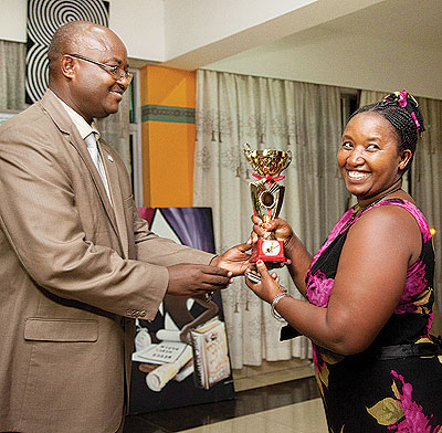 Uwamwezi receives her award from ICAR president Rugero Paulin for her contribution to the crafts sector recently. The food processing entrepreneur says planning and networking are key for one to grow a business.