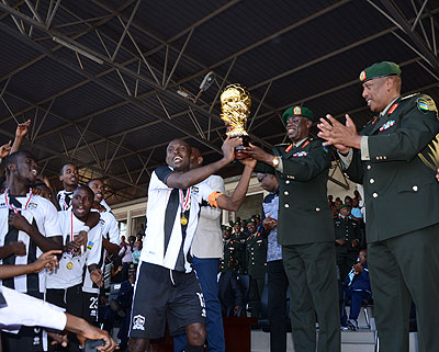 APR skipper Ismail Nshutiyamagara hands over the Peace Cup trophy to Minister of defence and club's honorary president Gen. James Kabarebe. S. Ngendahimana
