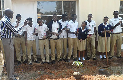 Balongo the head of student club activities at Lycée de Kigali, demonstrates to club members how to plant trees. Courtesy.