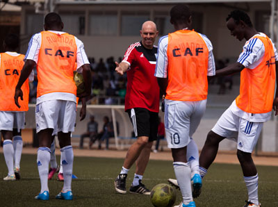 Coach Stephen Constantine shares a light moment with his players during a previous training session.  T. Kisambira