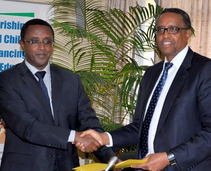 Dr Vincent Biruta (L) hands over to Silas Lwakabamba. (Courtesy)