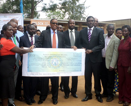 The Minister for Education, Prof. Silas Lwakabamba (C) and some of the beneficiaries of the new funding pose with dummy cheque. (Ivan Ngoboka)