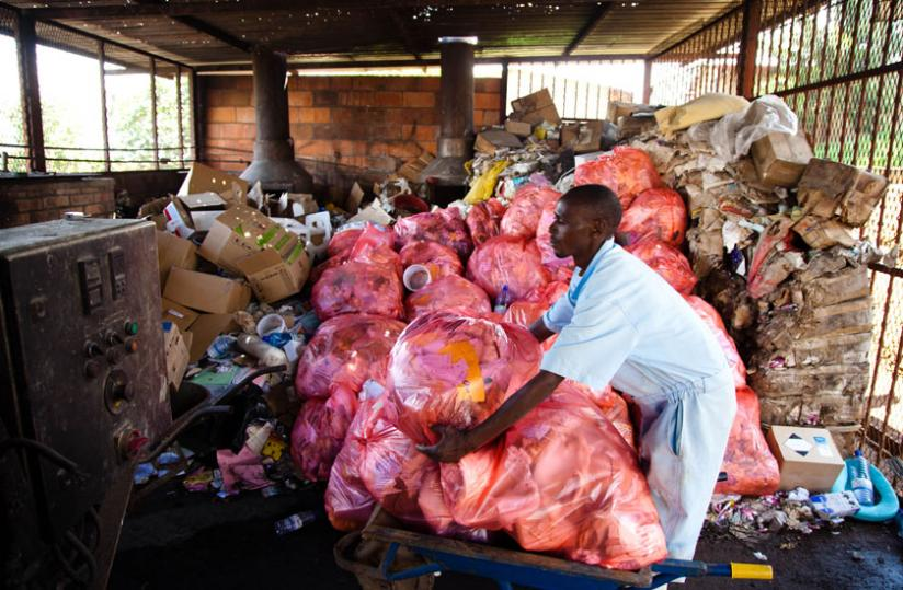 A worker at University Teaching Hospital of Kigali prepares waste to be disposed of in an incinerator. (Timothy Kisambira)