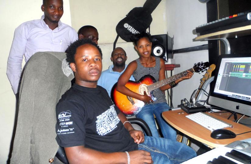 Dusabe, aka Moosa Ewan, poses with some of his artistes in the studio. (Moses Opobo)