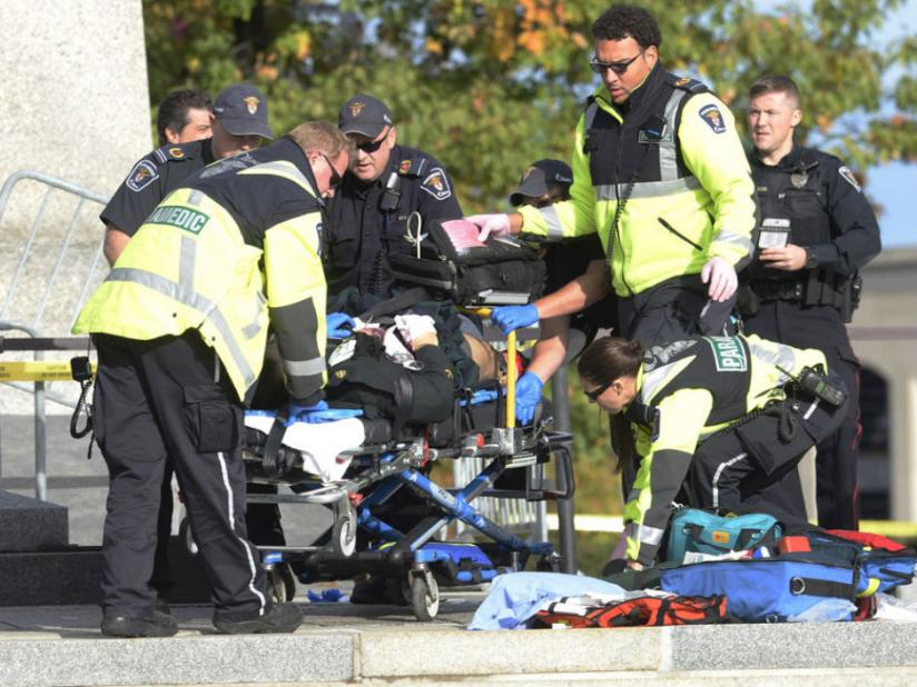 Police, bystanders and soldiers aid a fallen soldier at the War Memorial as police respond to an apparent terrorist attack in Ottawa (Internet)
