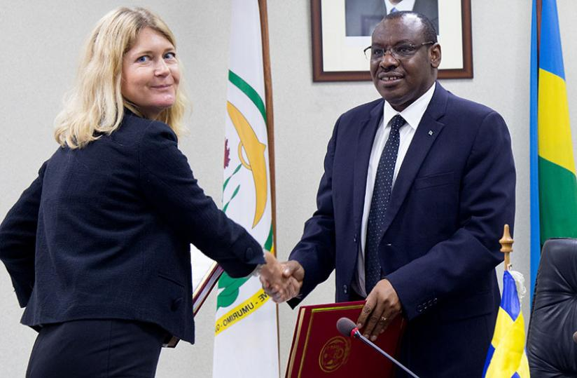HÃ¥kansson ( L) exchanges documents with Finance minister Gatete after the signing ceremony yesterday. (Timothy Kisambira)