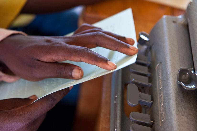 A blind person learns how to read. Efforts have been put in place to address their plight. (Timothy Kisambira)