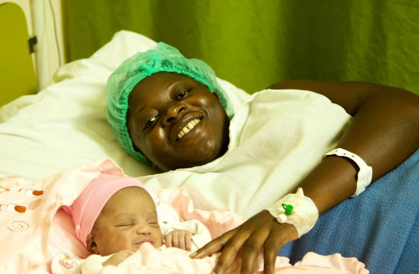 Tuyisabe smiles by her newborn  baby girl's side at King Faisal Hospital. (Doreen Umutesi)