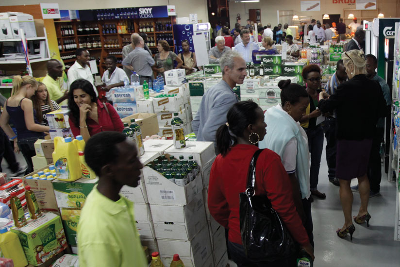 An attendant (left) watches as buyers check out items at a city supermarket. Clients are key in improving customer service.