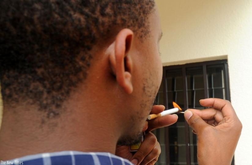A smoker lights a cigarette. The government has been urged to increase taxes on cigarettes to fight smoking. (File)