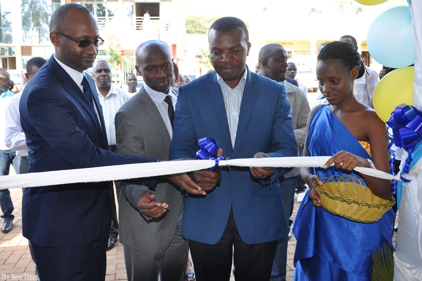 Bugunya (left) is joined by Rwamagana mayor Abdul Karim Uwizeyimana (second right) and other officials to cut the tape at the launch of Prime Insurance's 28th branch in the district. (Ivan Ngoboka)