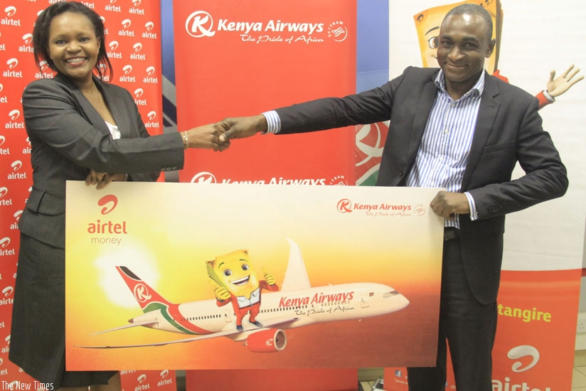 KQ's Kariuki and Airtel's Oware at the launch of the service. The product is expected ease booking of Kenya Airways airtickets. (Courtesy)