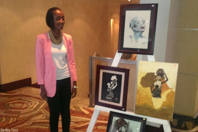 Pearl Karungi, one of the painters,  stands next to some of her work.