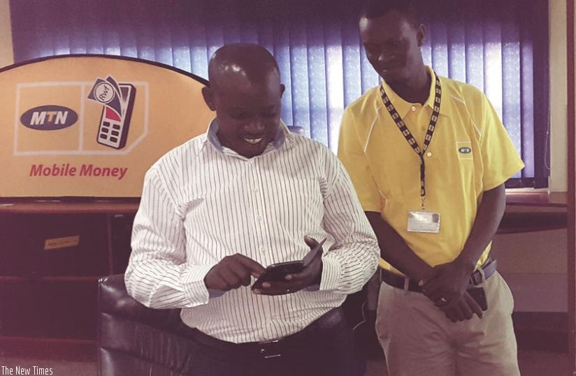 Emmanuel Butare, the headmaster of GS Muyange, tries out how one can pay school fees using mobile money yesterday at MTN head office in Nyarutarama. (Courtesy)