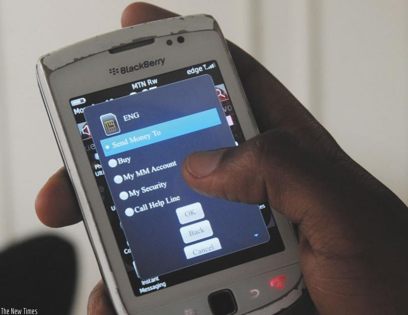 An MTN client makes a mobile money transaction. Mobile money subscribers will soon be able to send or receive money to and from Kenya and Tanzania. (File)