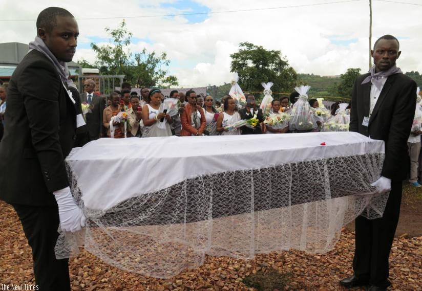 Pallbearers carry one of the caskets containing the remains of Genocide victims during the reburial at Rukira Genocide memorial in  Huye District on Saturday. (Emmanuel Ntirenganya)