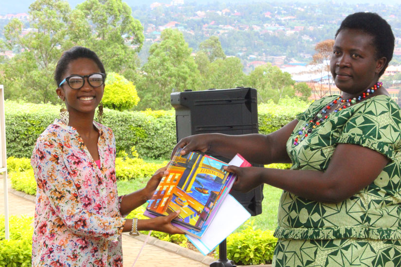 Dominique Alonga  hands over the books to Alodie Nyirandegeya