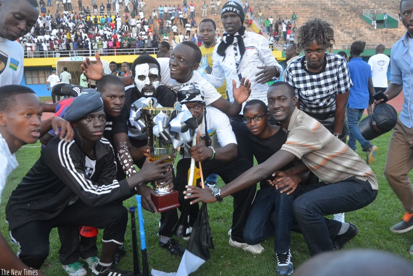 APR fans, who turned up for their team's final league game of the season, pose with the trophy after the army side were crowned champions.