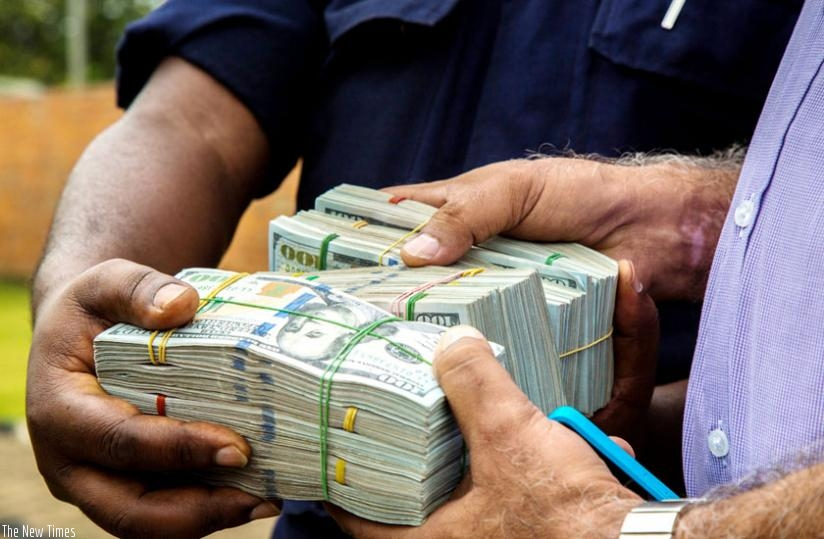 Police hand over recovered money to Somji in Kigali yesterday. (Timothy Kisambira)