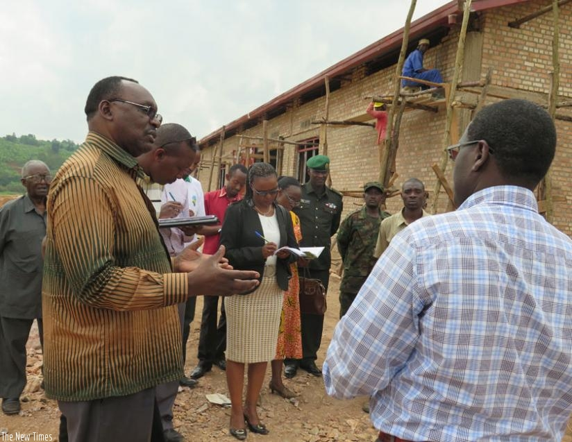 Minister Kanimba (L) chats with Gisagara officials at the construction site for the  proposed facility. (E. Ntirenganya)