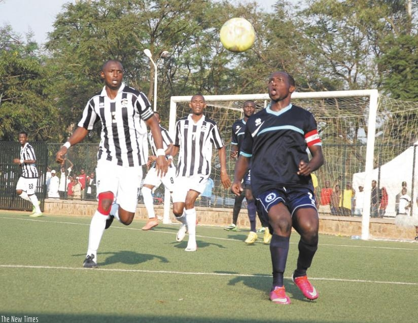 Police defender Fabrice Twagizimana (R) attempts to clear the ball against APR skipper Ismail Nshutiyamagara during the first leg. The second leg ended 0-0 yesterday to send Police to the final. (Peter Kamasa)