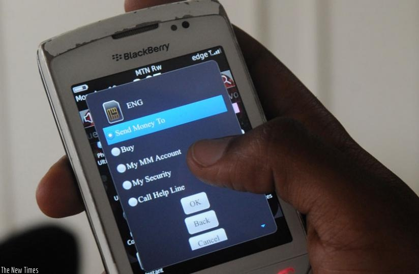 A mobile phone user sends money using mobile money services. (File)
