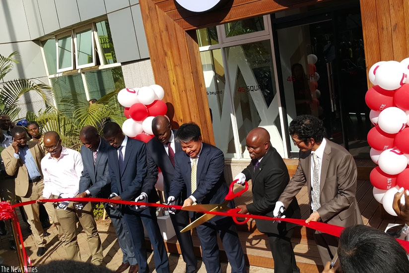 With giant scissors, the minister of youth and ICT, Jean-Philbert Nsengimana (2nd from right) cuts the ribbon unveiling the 4G Square in Kigali flanked by the chief executive officer of Olleh Rwanda Networks to his left and other officials. (Courtesy)