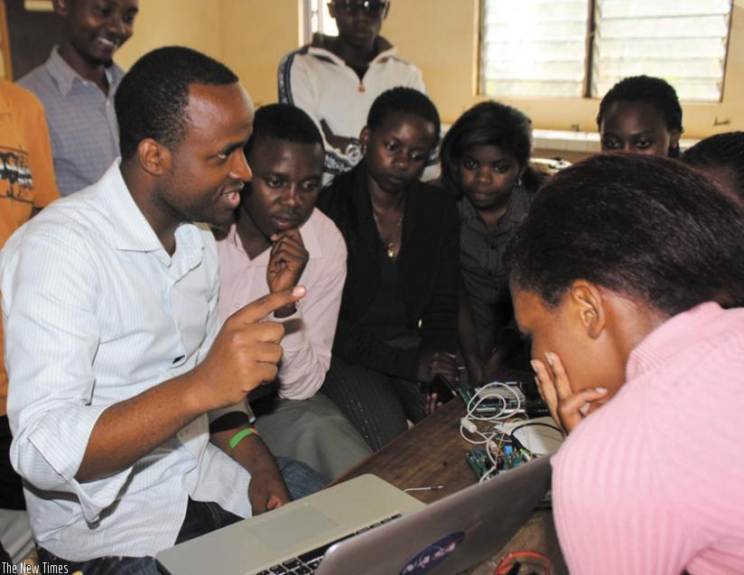 Creation Hill's proprietor Twagirayezu (left) briefs IT enthusiasts at one of the technology fairs he conducted last year. The founder is a previous winner of the Digital Change-makers competition. / Courtesy.