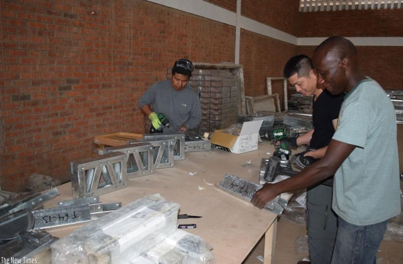JS workers assembling components of a house at their KSEZ-based factory. (Stephen Kalimba)
