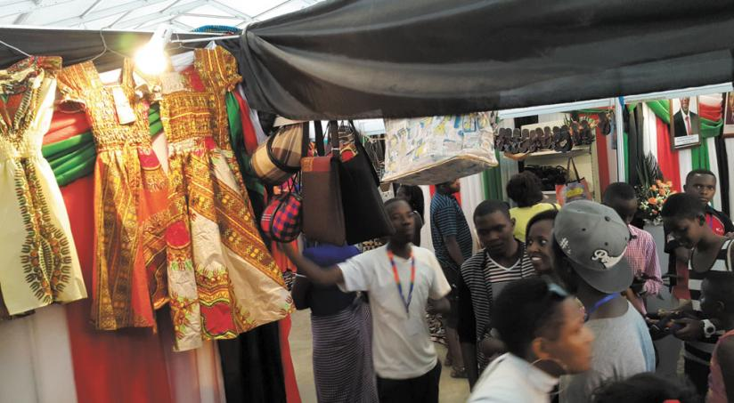 A salesperson (left) beckons showgoers at the ongoing expo at Gikondo. Exhibitors say business has been low. (Ben Gasore)
