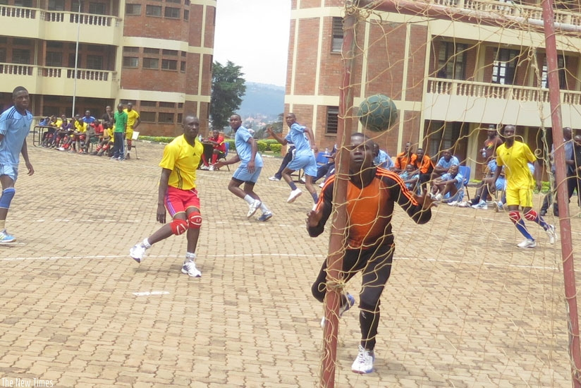 Police players (in blue) try to advance after concending against UR-CE (in yellow) at the UR-CE handball court. (S. Kalimba)