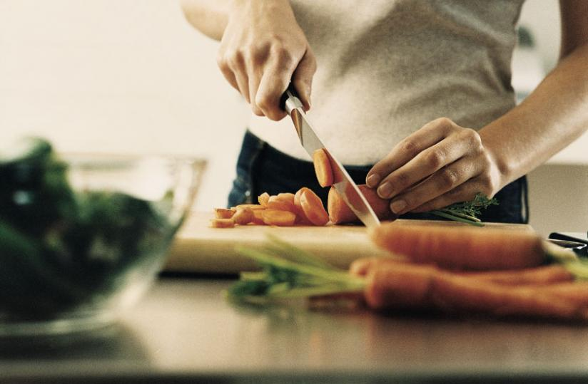 A man chops carrots into small pieces. You must be careful about how you prepare vegetables and food/