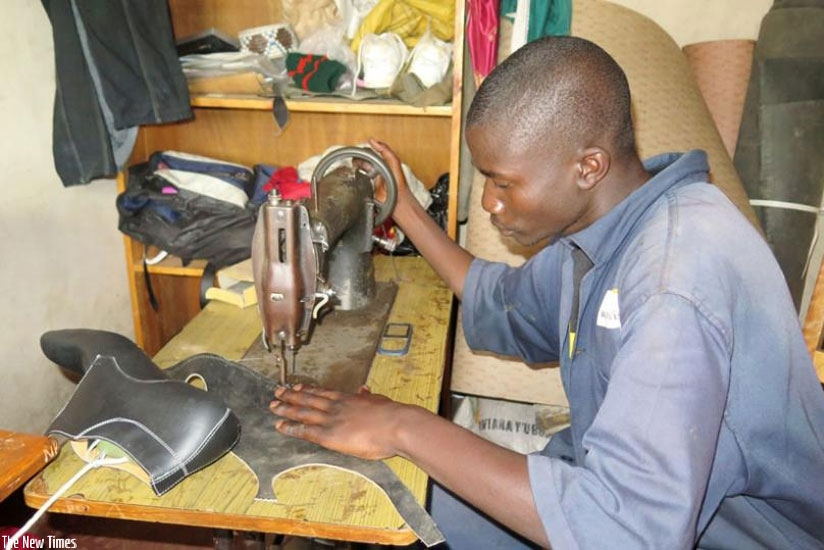Alphonse-Karangwa of Twitezimbere Cooperative in Kibeho sector in Nyaruguru sews leather to make shoes early this year. Tax on second hand leather products has been raised to 100% imposed to support local industries. (File)