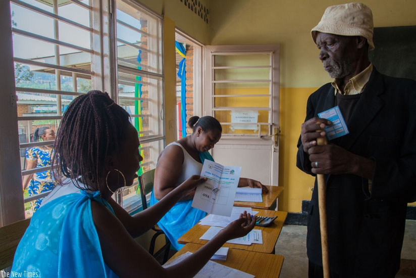 A polling agent at La Colombiere polling station guides an elderly man on the voting procedures. Voter turn-up was 98.3%. (Faustin Niyigena)