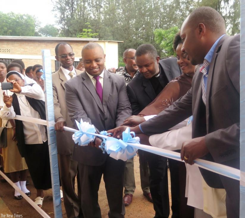Rwamukwaya (C), with parents and other officials cut the ribbon to open the dormitory. (F. Byumvuhore)